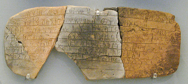 Photograph of a clay tablet broken into three pieces, covered with script.