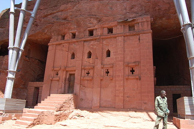 Exterior view of the entrance, which is carved directly into the rock. A giant portion of the uncarved rock sits atop the entrance.