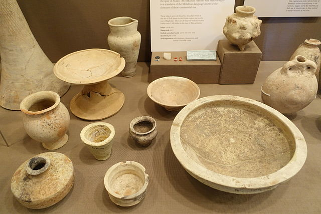 Photograph depicting a large pottery collection featuring a small pedestal, cups and bowls in various sizes, and a large round plate or tray.