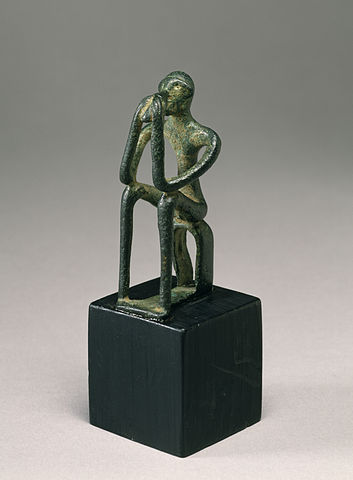 Photo shows a bronze figure, seated with its head in its hands. Its limbs are thin and elongated.