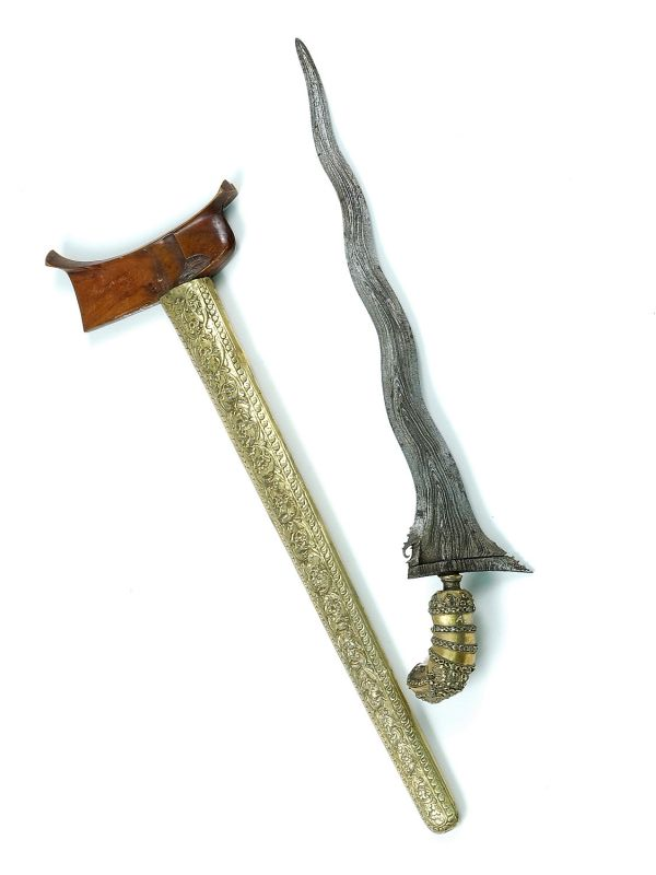 This photo shows a kris and an axe. The kris is an asymmetrical dagger noted for its distinctive wavy blade patterning.