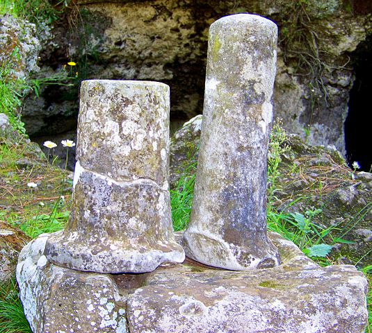 This is a photo of two short cylindrical columns (cippi) outside a tomb.