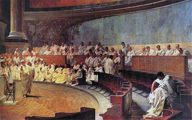 This is a photo of a nineteenth-century fresco in the Palazzo Madama in Rome. The Roman senators clothed in white togas sit in the circular gallery facing the floor where Cicero speaks, denouncing Catiline. Catiline is depicted sitting alone with slumped shoulders.