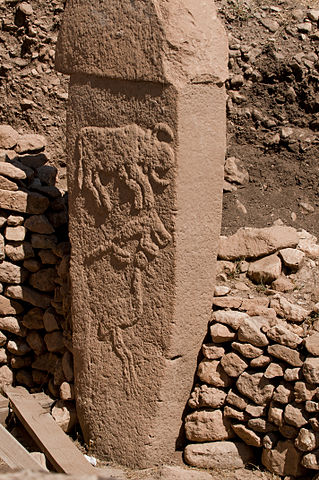Photo shows mud brick t-shaped pillar with animals etched into it. It rests against the remains of a stone wall.