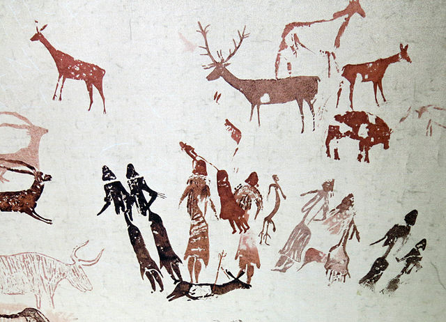 Prehistoric rock art depicts human figures surrounding an animal that has been speared. Other large game with horns and antlers surround the human figures.