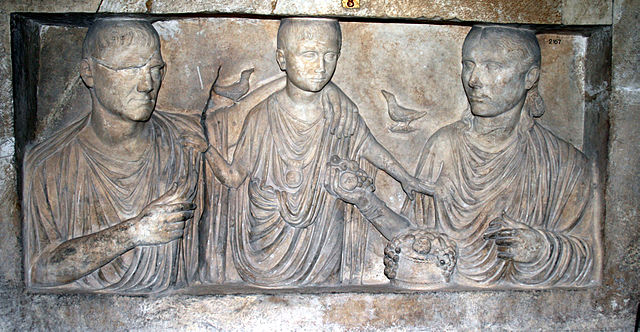 This is a photo of a relief of a Roman family. The father (left), the child (center), and the mother (right). The family wears Roman togas. There is a bird perched on the father's arm, which rests on the child. A second bird is in the sky above the child's right shoulder.