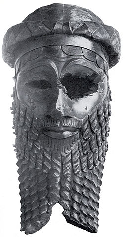 Photo portrays a bronze rendering of the face of an Akkadian ruler with strong features and a disfigured eye. The figure has an imposing beard and wears a headband.