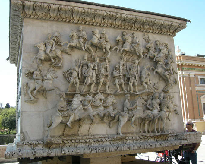 This is a current-day photo of the pedestal of the Column of Antoninus Pius. It shows the decursio scene in which members of the cavalry (men on horses) circle the standing figures, two carrying military standards and the rest fully armored.