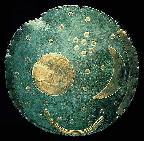 Photo depicts bronze disc decorated with a moon, sun, and starscape.