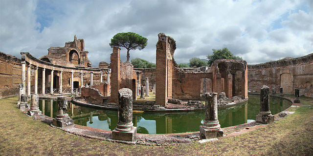 This is a photo of the current-day ruins of the Maritime Theater at Hadrian's villa. It is an island enclosure, displaying classical ionic style. The photo shows the remains of a circular shaped structure and ionic columns surrounded by a circular pool.