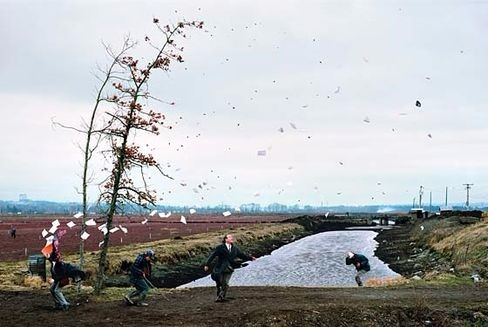 Photo shows three figures near a river, bracing themselves against a strong gust of wind. Two thin trees are bending and a stack of papers is flying out of a person's hands.