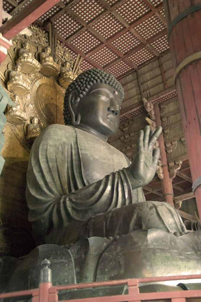 The buddha is depicted sitting, eyes closed, with one hand raised.