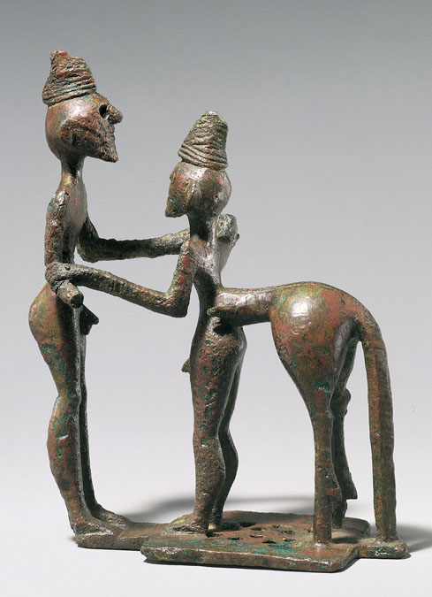 This is a photo of the small bronze statue Man and Centaur (Heracles and Nessos). The two figures feature elongated arms, with the right arm of the centaur forming one continuous line with the left arm of the man.