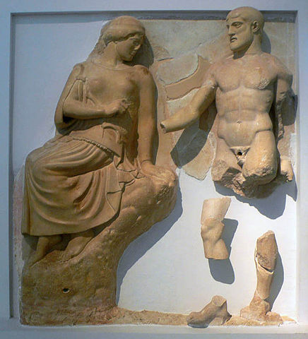 This is a photo of Athena and Herakles depicting the Stymphalian Birds. On the left, Athena sits on a high rock. She is dressed in draped garments. On the right Herakles turns slightly toward center in order to present Athena with dead birds, which have broken off the metope.