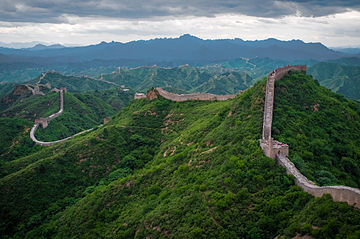 The wall is pictured winding through lush green hills into the distance.