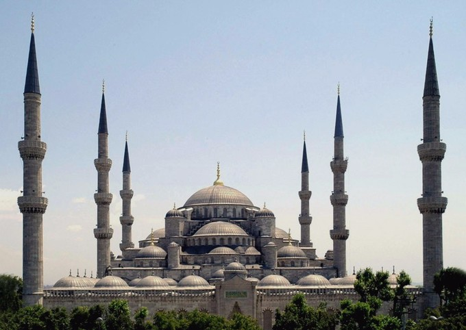This is a photo of the Blue Mosque. In the center is a large dome, beneath are several smaller domes. All together, they form a triangular or pyramid shape. There are three slender minarets on either side of the domes.