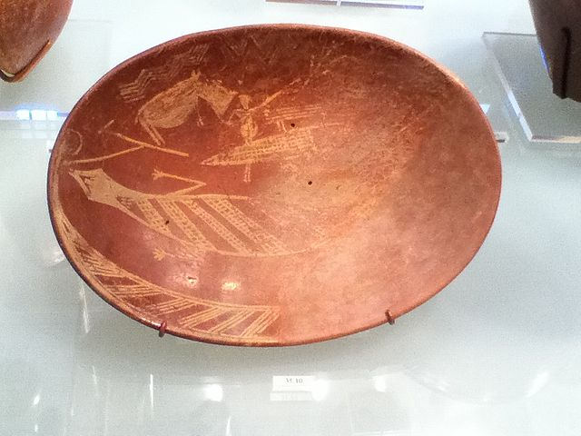 This is a plate from the Early Dynastic period of Ancient Egypt, circa 3900 BCE. It depicts a man on a boat alongside a hippopotamus and crocodile. In this context, the hippopotamus probably symbolizes chaos and destruction in the form of the god Seth, while the crocodile could symbolize the god Sobek, who occasionally served as a protective deity.