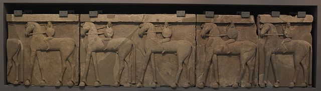 Photograph of a portico frieze. It features a relief with a repeating pattern of a figure riding a horse.
