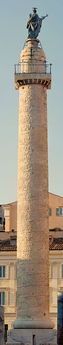 This is a current-day photo of the Column of Trajan. The structure is about 35 meters tall, including the pedestal. The shaft is a colossal Carrara marble drums decorated in reliefs that depict military battles. It is topped with a statue of Trajan.