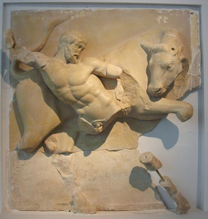 Photo depicts a metope of Herakles fighting a bull. Pieces of Herakles' limbs and body have broken off the metope.