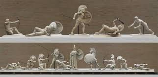 Photo of sculptures from the pediment that show Greek warriors and Trojan warriors at battle, wielding shields, spears and bows.