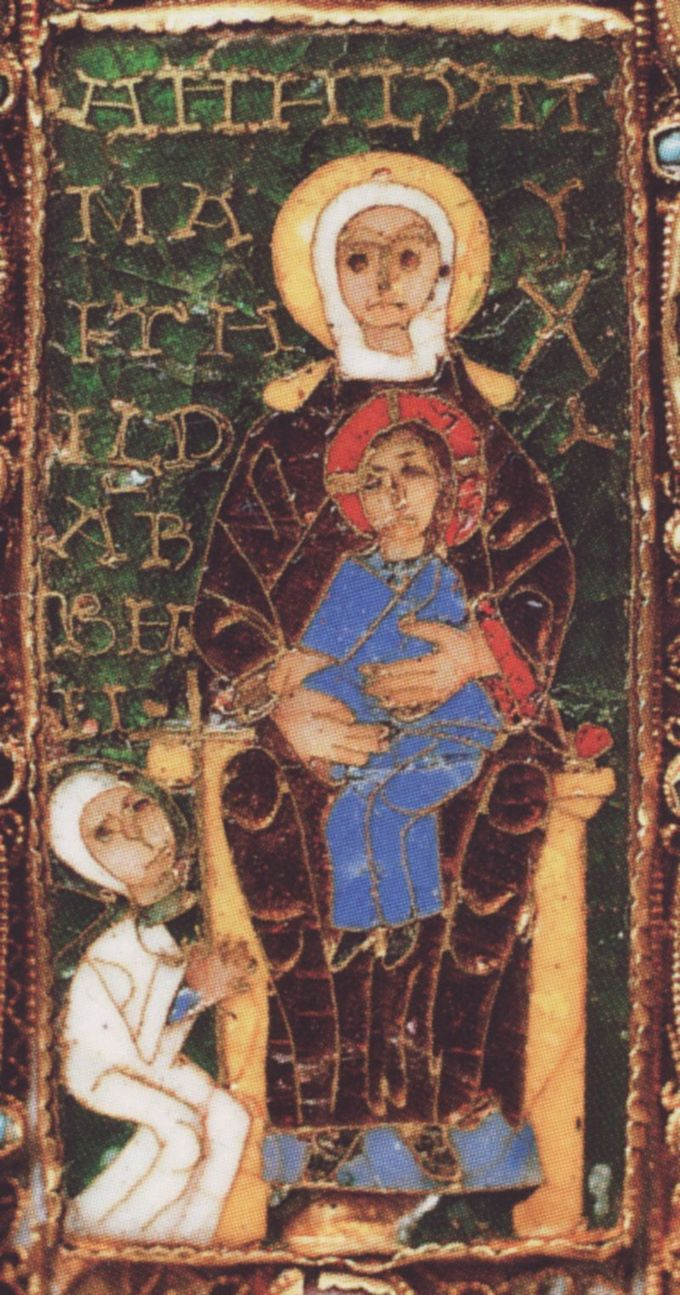 An enthroned Madonna in frontal view, holding her son on her left knee, in front of a figure dressed in white robes. The figure holds a cross with both hands, which she offers to the baby Jesus. The child stretches both hands towards the cross in a gesture of acceptance.