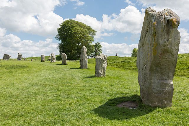 Photograph depicts stones at Avebury. Stones are arranged to form a large circle. The photo is taken at an angle that displays part of the circle.