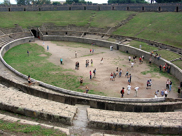 This a current-day photo of the Amphitheatre of Pompeii. It shows the interior, with its tiered seating, which shows the influence of Greek designs.