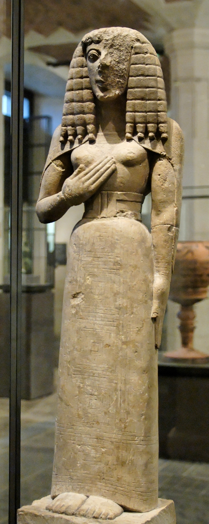 This is a color photo of The Lady of Auxerre, a limestone statue depicting a woman. Her hair is stylized and she wears a long, narrow dress cinched in at the waist, her feet stick out from under its hem. Part of the statue's face has crumbled.