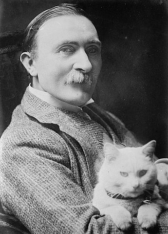 Black and white photograph. Burne-Jones looks at the camera while holding his white fluffy cat.