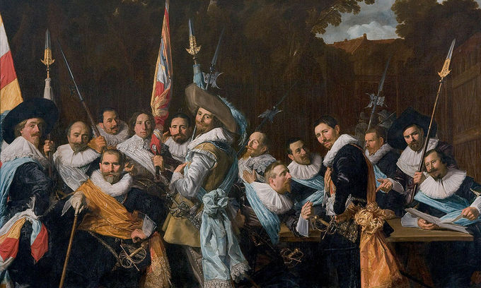 In this group portrait, the men are seated outside in the courtyard wearing sashes.