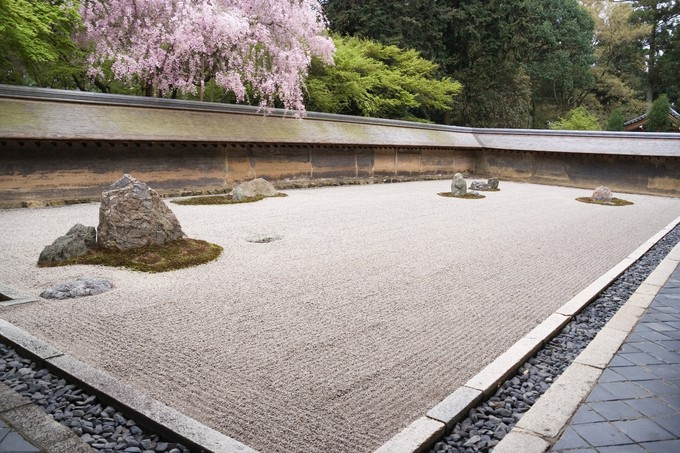 Image of the Ryoan-ji zen garden at the temple. The garden features larger rock formations arranged amidst a sweep of smooth pebbles raked into linear patterns.