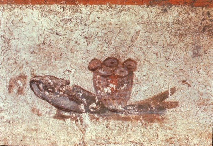 This is a photo of iconography from the Christian Catacombs. It depicts five loaves of bread and two fish, alluding to Jesus feeding the multitude.
