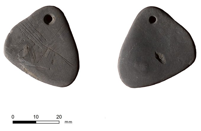 Photo depicts front and back view of a shale pendant. The pendant is shaped like a triangle with rounded edges. There are a series of lines etched into the stone.