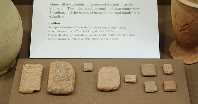 Several small stone tablets and tiles covered with cuneform writing.
