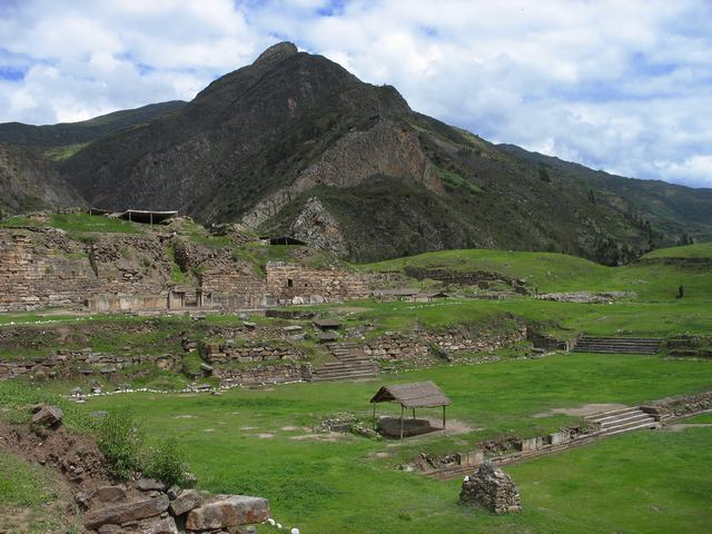 A view of the ruins of Chavin de Huantar with mountains in the background.