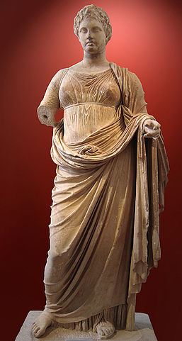 This is a photo of a marble statue of Themis. It depicts her full-length figure and she wears a long dress and has short hair.