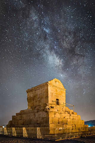 Photo depicts tomb of Cyrus the Great, the lower part is built of stones cut square and was rectangular in form. Above, there was a stone chamber with a roof and a door leading into it. The main decoration on the tomb is a rosette design over the door.