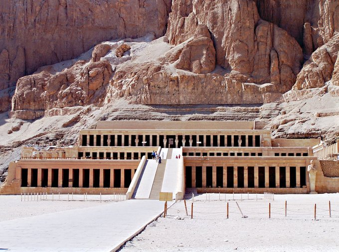 Photo depicts the Hatshepsut Temple, a structure of three layered terraces reaching 97 feet tall. Each story is articulated by a double colonnade of square piers. Behind the temple are the tall cliffs at Deir el Bahari.