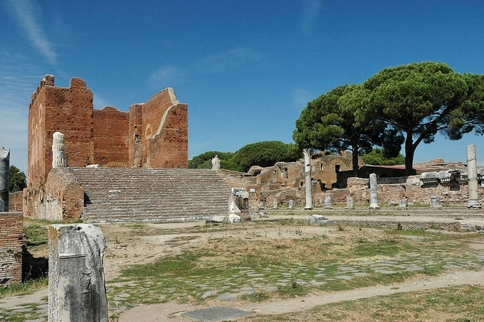 This is a photo of the ruins of the Capitolium at Ostia, including the steps up to the building and what remains of its walls and fluted columns.