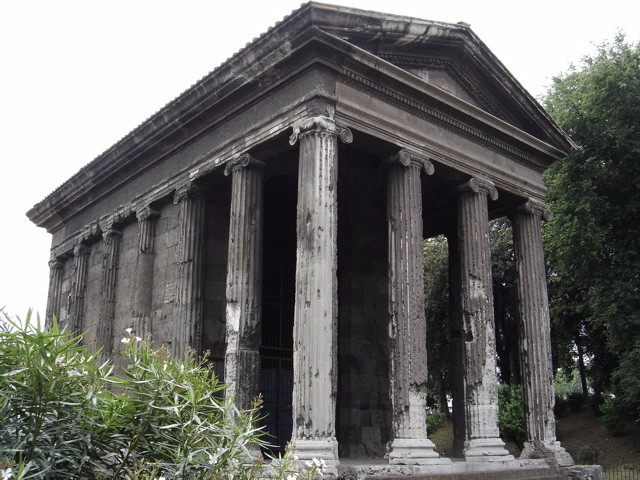 Photograph of the temple, a rectangular structure. The front is four columns wide and two columns deep.