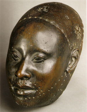 A realistic bronze sculpture of a face.