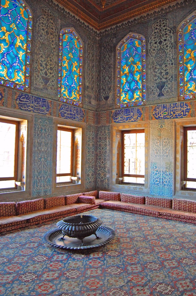 This photo shows the carpet and interior of the Harem room in Topkapi Palace, Istanbul. It shows intricate blue and yellow floral stained glass windows and patterned carpet.
