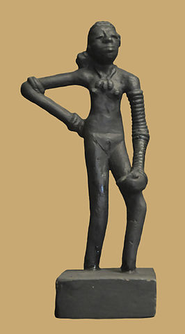 Photo depicts a bronze statuette of a nude woman standing with her hand on her hip.