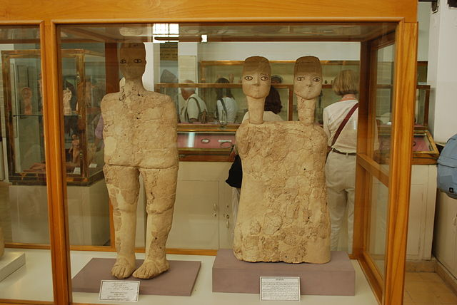 Photograph depicts statues and busts inside a display case at the Jordan Museum. On the left, is a full-length statue made from read and limestone. On the right is a two-headed bust made from the same materials.