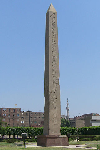Photograph depicts an obelisk of a tall, four-sided, narrow tapering monument which ends in a pyramid-like shape or pyramidion at the top.