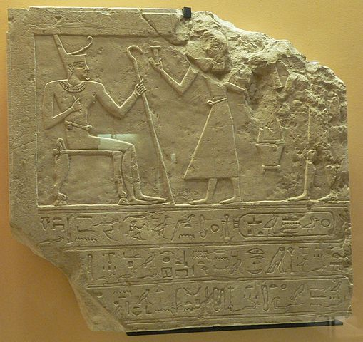 Mentuhotep II receiving offerings as he is seated, holding what looks like a cane.
