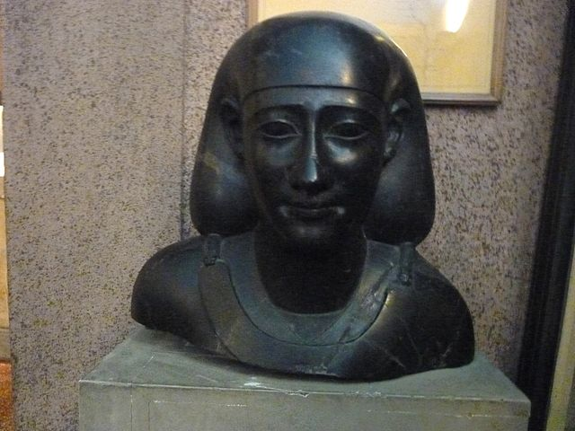 Black stone bust depicts the head of a man wearing a headpiece and prominent necklace.