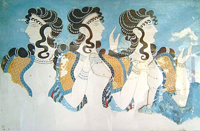 This is a color photograph of a fresco from the complex at Knossos. It depicts a popular fashion for Minoan women—short-sleeve dresses with flounced skirts whose bodices were open to the navel, allowing their breasts to be exposed. The women's faces are in profile view and their bodies are in frontal view.