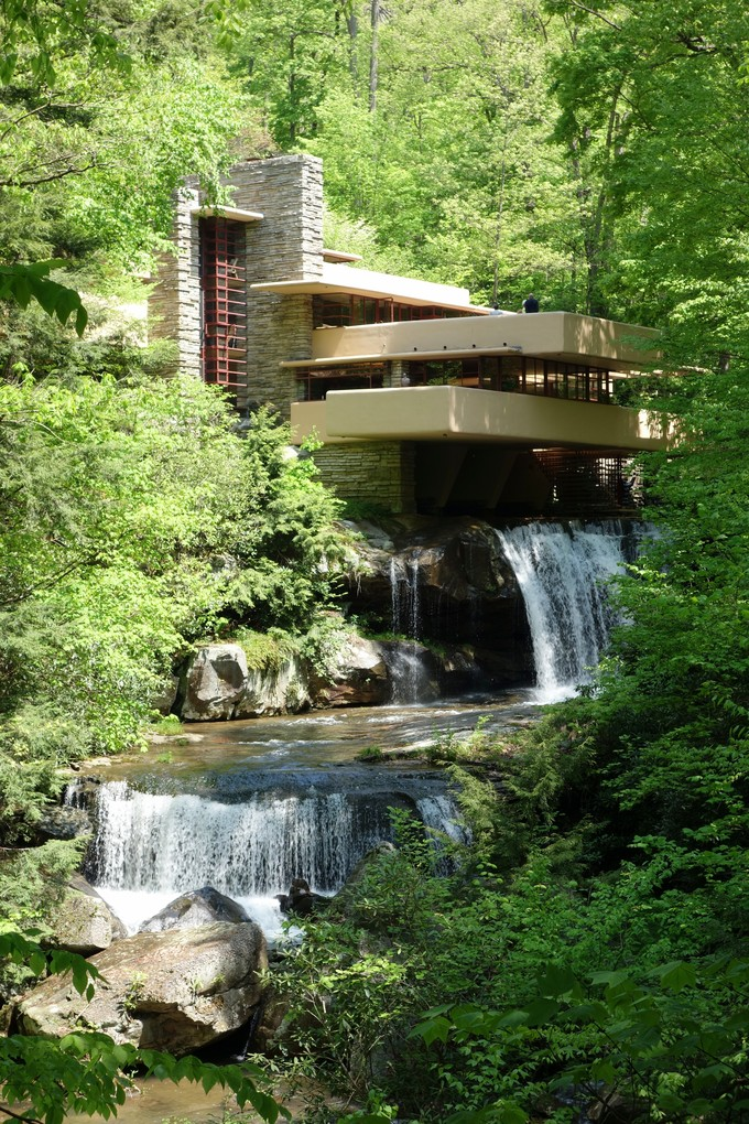 Image of the exterior of Fallingwater, a simple building with several layers built into a thick forest. A waterfall runs underneath and into the foreground of the photo.